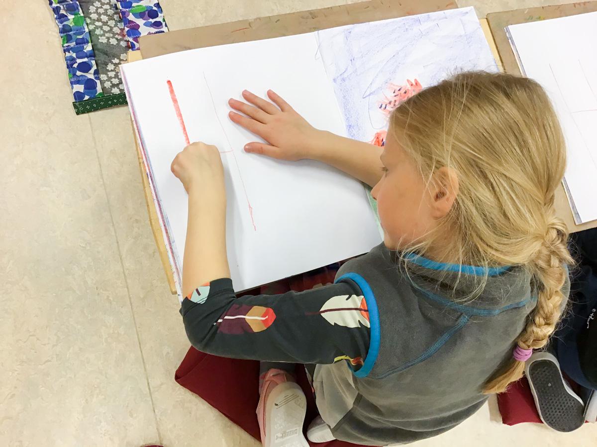 tyttö äidinkielen tunnilla harjoittelee H-kirjainta